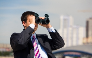Portrait of handsome businessman with binoculars in hands looking through it in the downtown