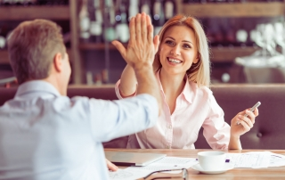54005744 - beautiful business woman is giving high five and smiling to man during business meeting at the restaurant